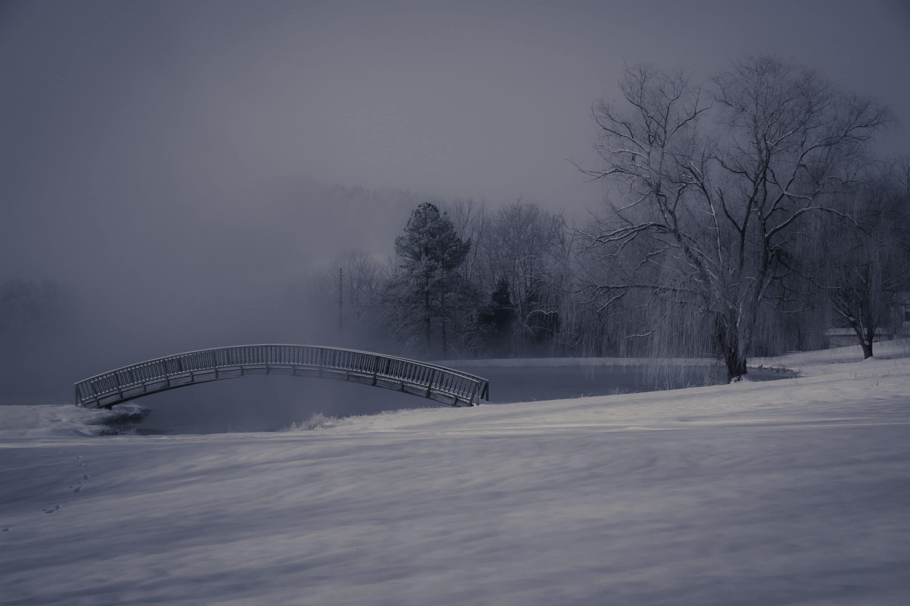 snow fog and ice around an arched bridge over a pond in a snowy landscape