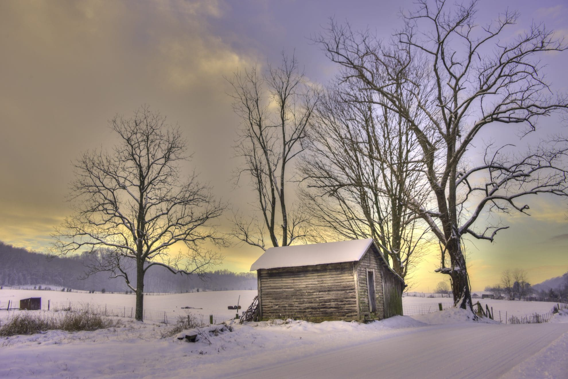 a snowy rural setting landscape print with wooden shed and sunset sky
