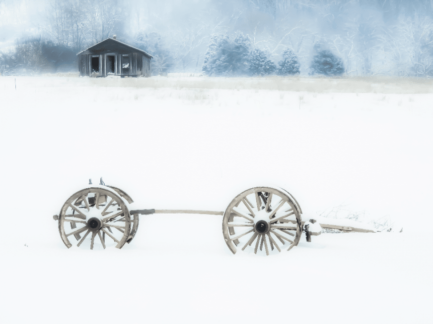 winter canvas photo print of wagon wheels partially buried in snow