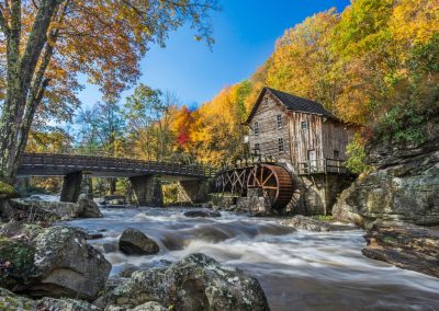 old grist mill in autumn by whitewater stream