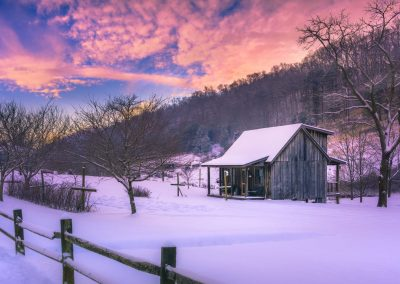 pink and blue sunset over tiny cabin in snowy scene