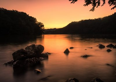 water wall art peach toned sunset over lake with rocks