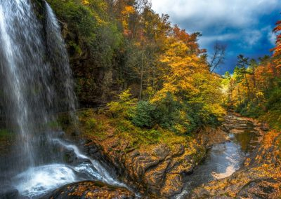 waterfall wall art with bright blue sky and autumn trees