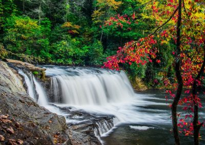 wide low waterfall with red autumn leaves