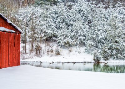 winter scene wall art evergreen trees covered in snow beside a red barn and a blue pond with geese