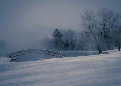 winter scene wall art of curved bridge over small pond in deep snow