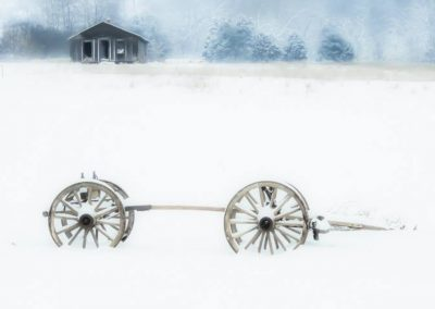 winter wall art image of old wagon wheels sitting in snow with trees in background